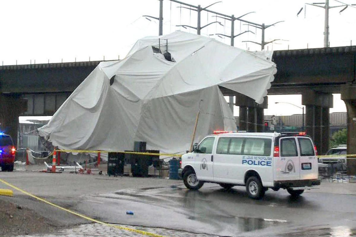 Officials respond to the scene where a tent blew over after high winds crossed the area, Saturday, April 28, 2012, in St. Louis. The tent was set up next to Kilroy's Sports Bar, where St. Louis Fire Chief Dennis Jenkerson said a few hundred people were ce