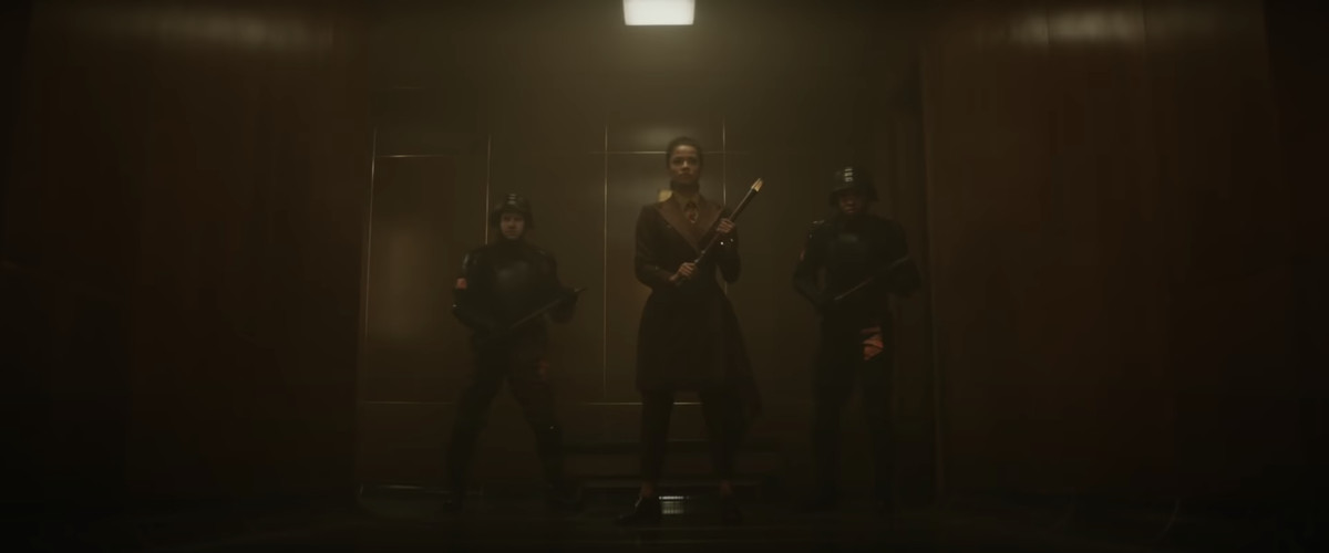 Gugu Mbatha-Raw's Loki character is flanked by two guards.