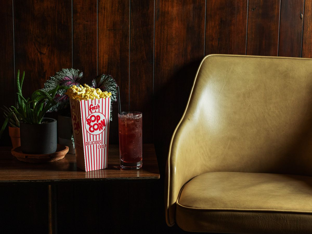 A red and white striped box of buttery popcorn and a tall cocktail with a black straw sit on a mid-century table next to an antique pleather chair.