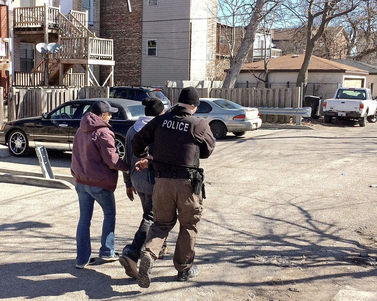 A heroin buyer being taken into custody by police officers on the West Side. | Frank Main/Sun-Times
