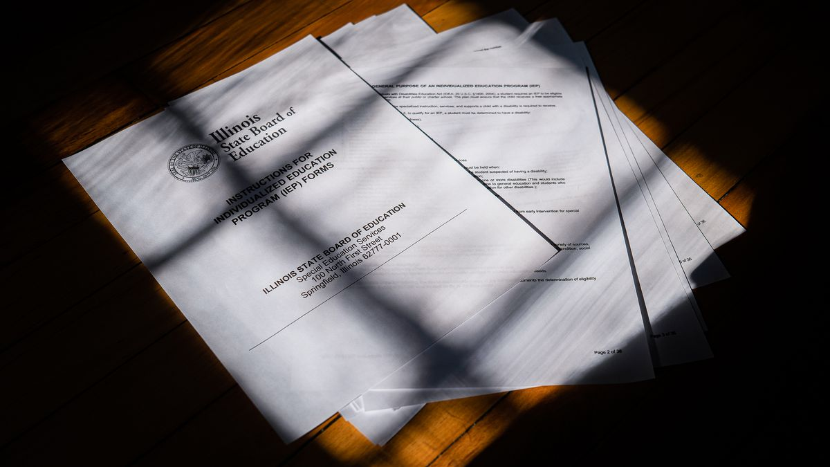 Informational documents from the Illinois State Board of Education on Individualized Education Program (IEP) forms are partially obscured by shadows.