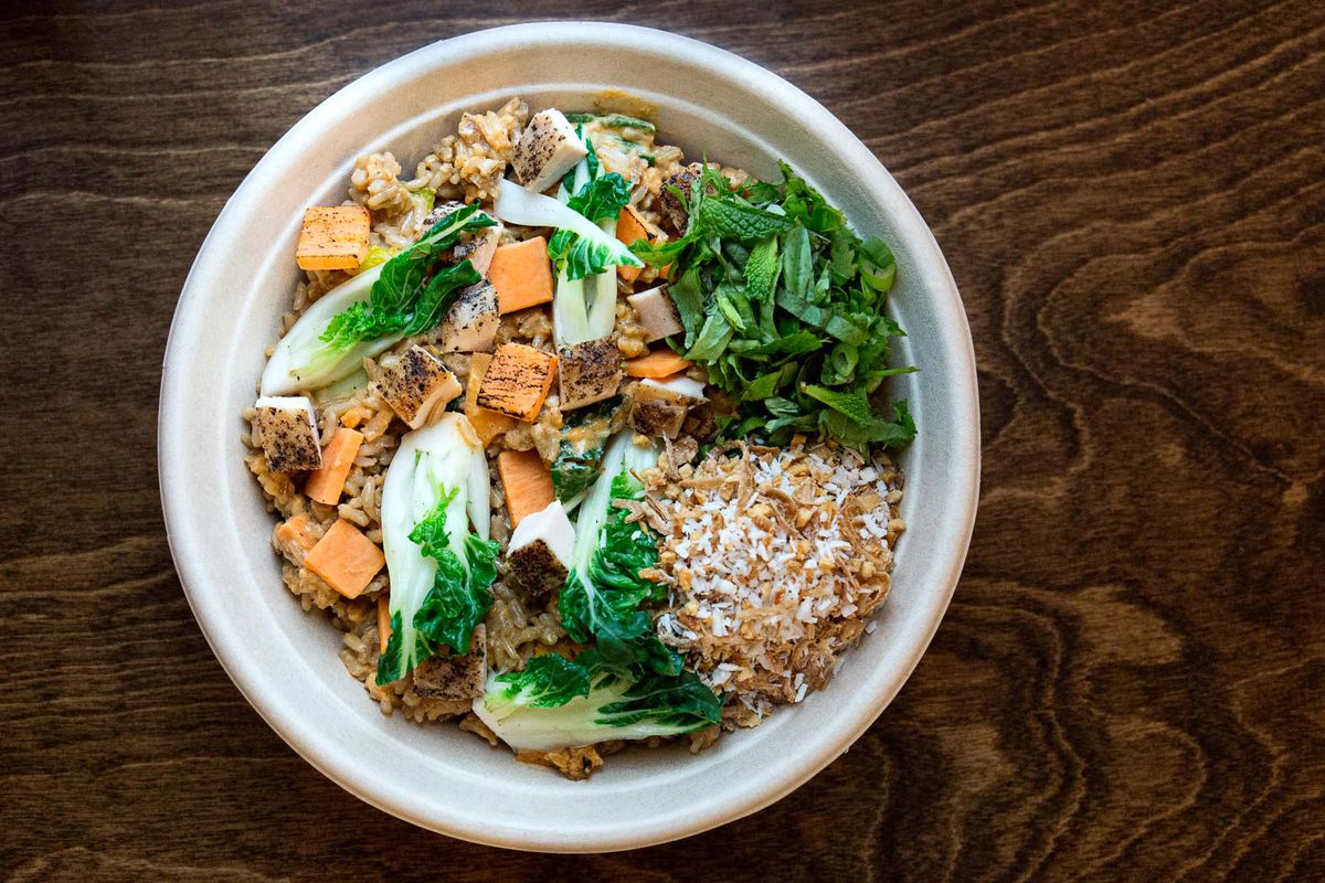 An overhead view of a grain bowl with roasted chicken, sweet potatoes, bok choy, and more