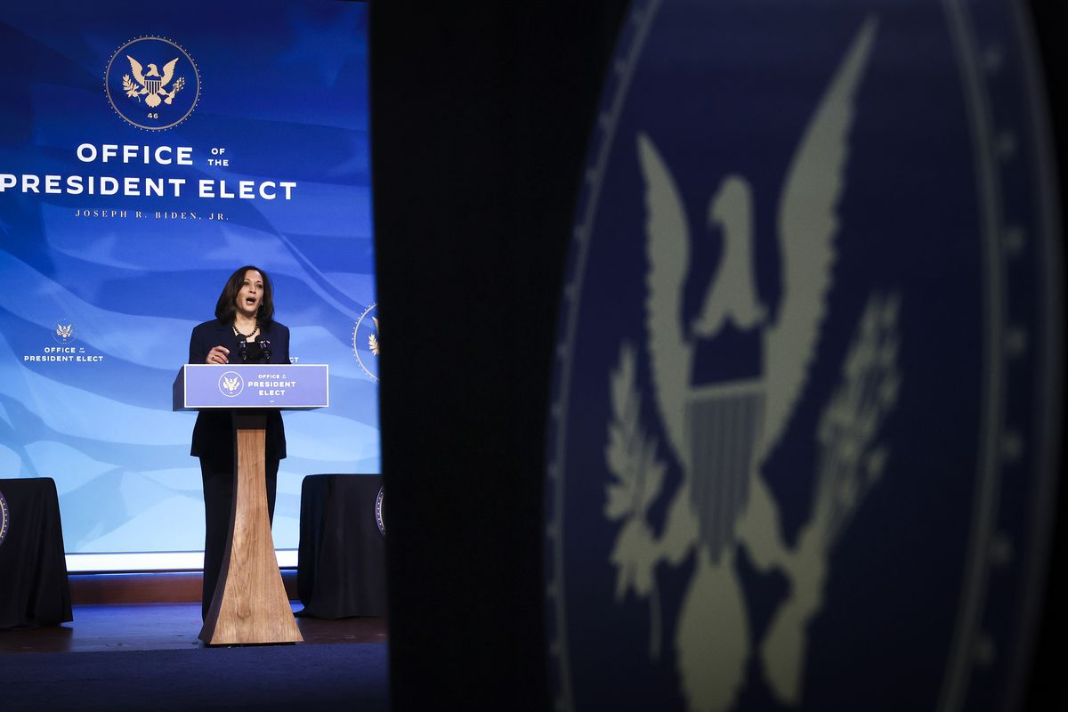 """Kamala Harris standing at a lectern in front of a wall that reads """"Office of the president-elect."""""""