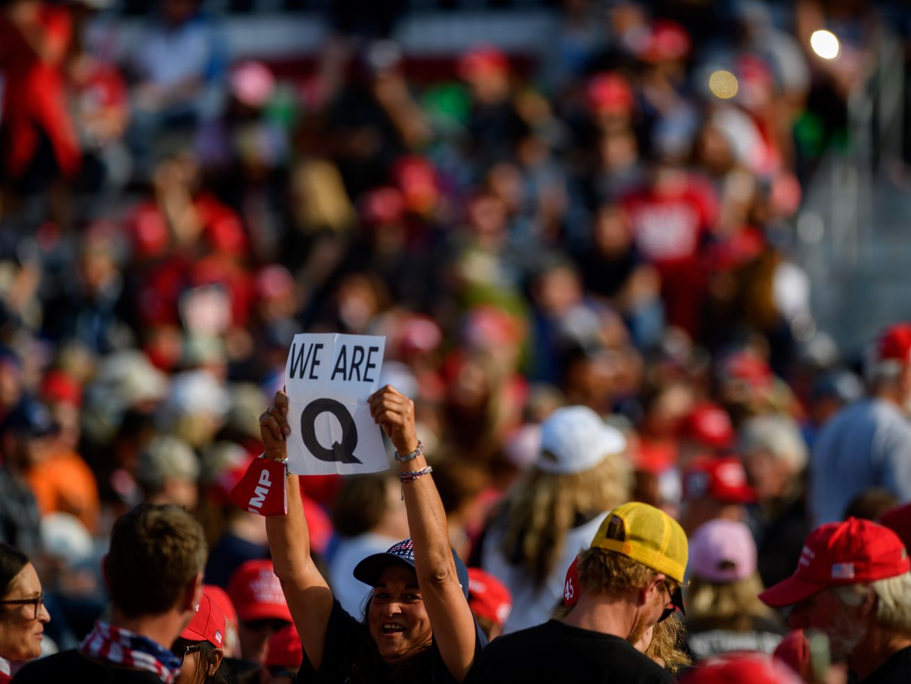 """A person in a crowd holds up a sign that reads """"We are Q."""""""
