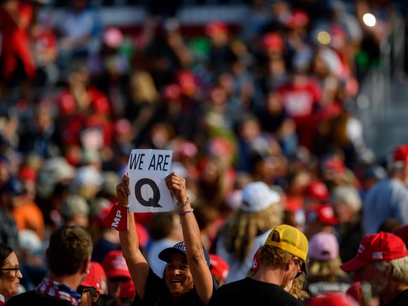 Une personne dans une foule brandit une pancarte indiquant «Nous sommes Q.»