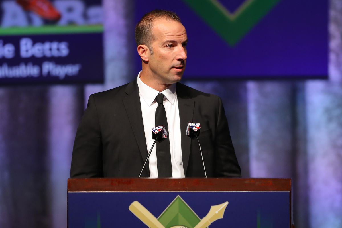 Billy Eppler wearing a black suit and black tie but no sunglasses standing at a podium with two microphones.