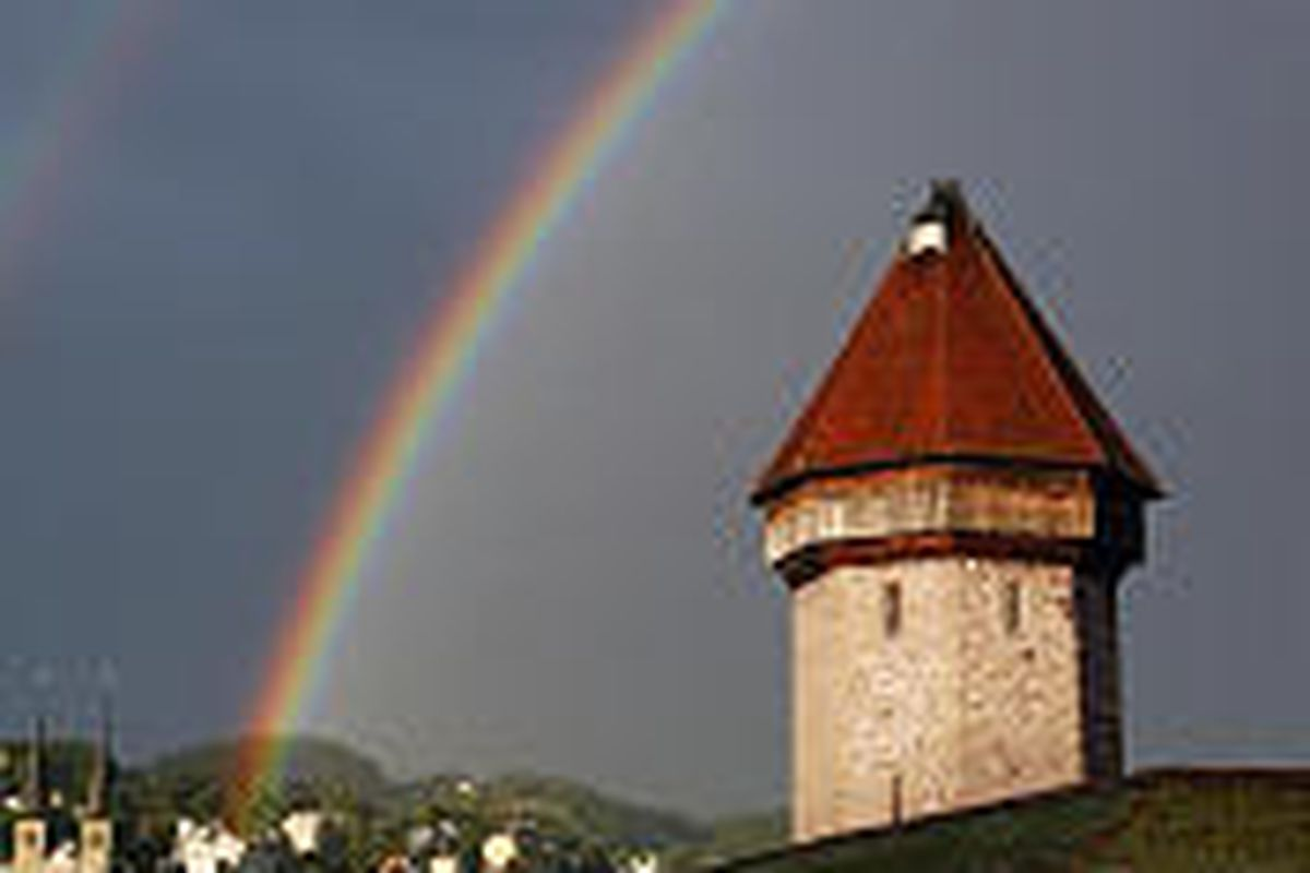 A rainbow spreads over the Chapel Bridge, built in 1333, and the Water Tower in Lucerne, Switzerland.