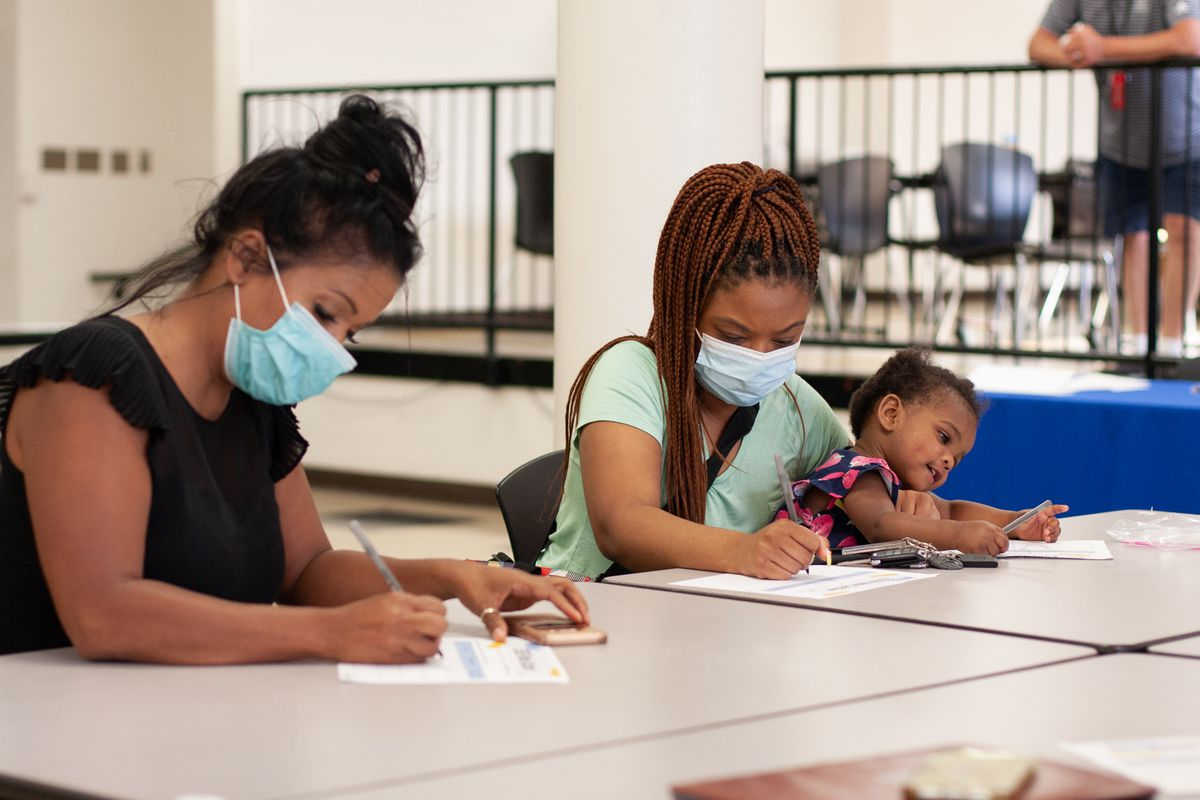 A woman in a black shirt wearing a blue face mask with her hair in a bun and a woman in a teal shirt with a blue face mask holding a distracted young child on her lap sit at a table and write on pieces of paper.
