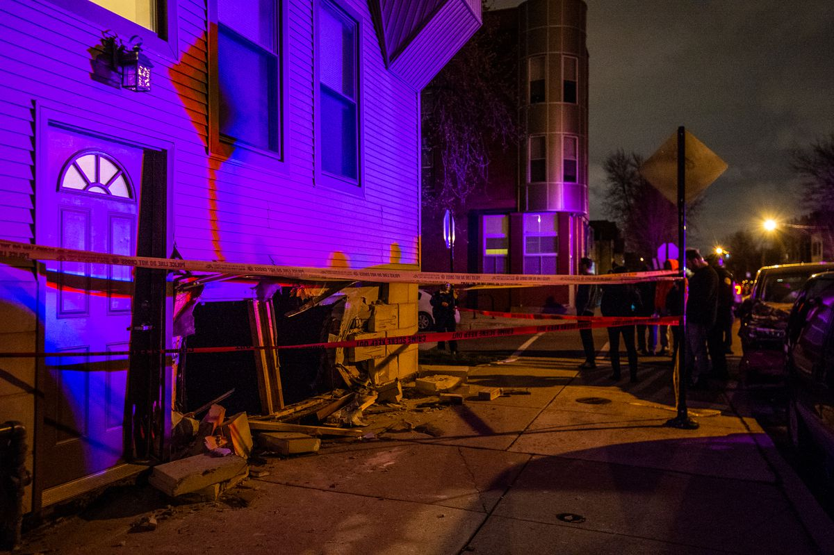 Residents survey the hole that was left after a vehicle crashed into an apartment building Thursday night in Logan Square | Tyler LaRiviere/Sun-Times