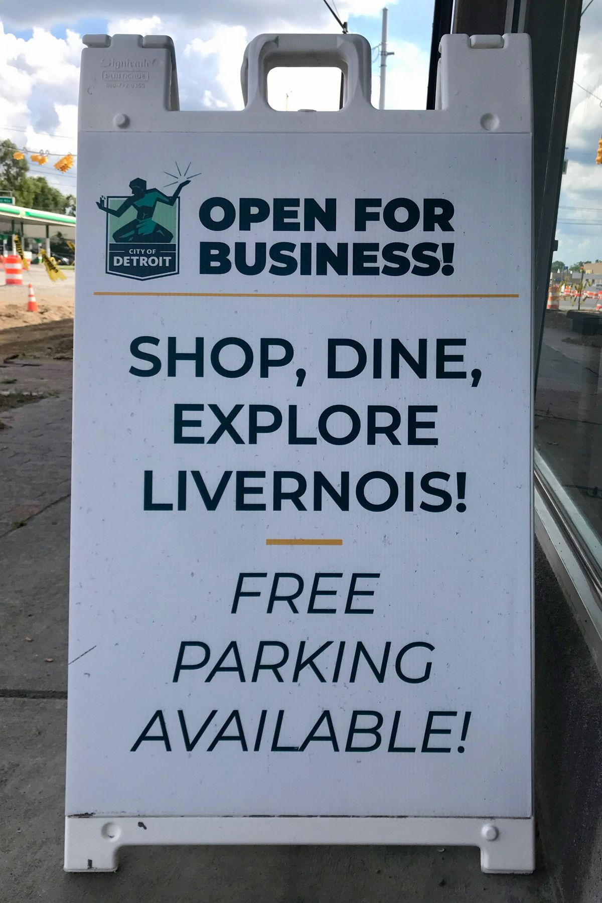 """A sign that says """"Shop, Dine, Explore Livernois! Free Parking Available!"""""""