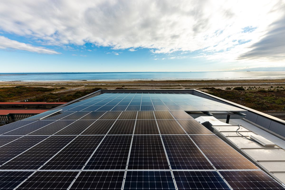 The rooftop of a passive house apartment building clad in solar panels, looking out towards the Atlantic Ocean.