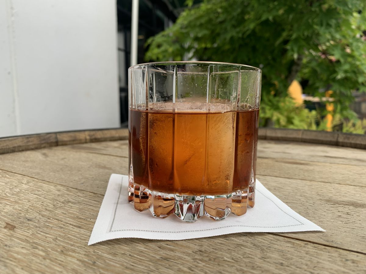 A faceted rocks glass rests on a wooden barrel. The glass holds a red drink and a large ice cube, and there is a small maple in the background.