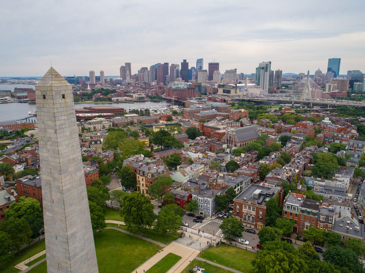 An aerial view of city buildings in Boston. In the foreground is a tall monument. In the distance is a body of water and a skyline with many buildings.