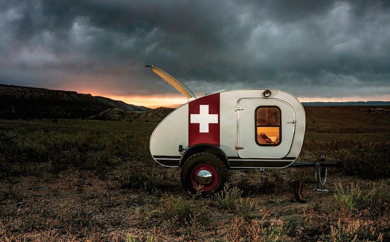 A Vintage Overland camper van. The van is white with a red stripe that has a white cross symbol. It is in the middle of a field. There are mountains in the distance. The sky is full of dark grey clouds.