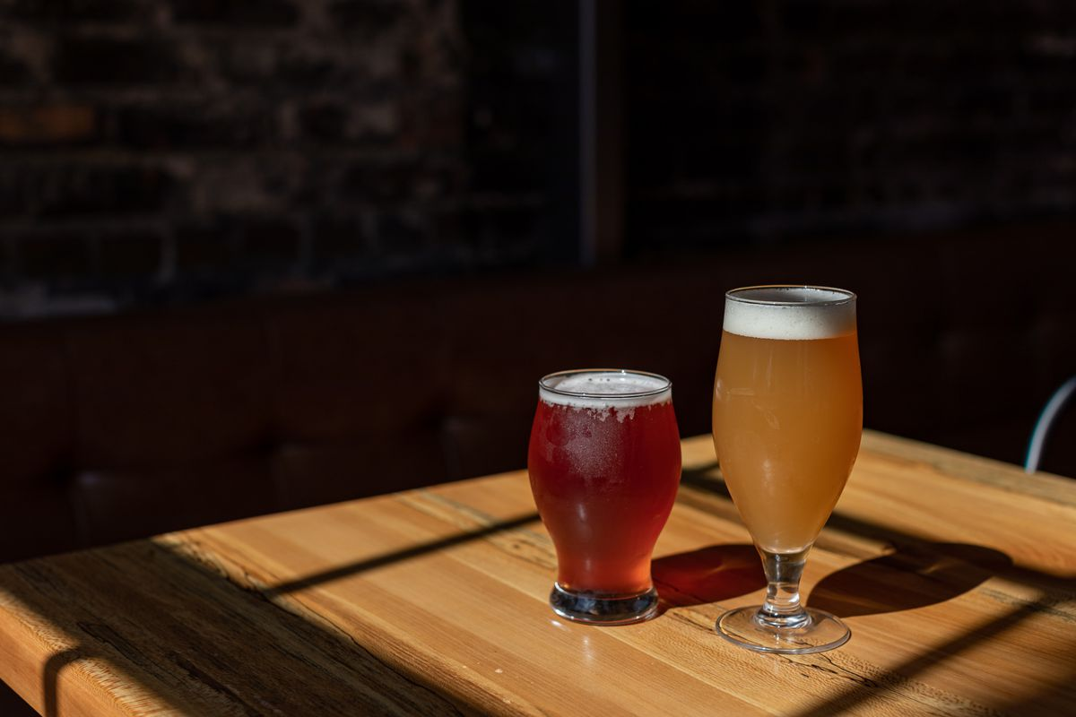 A red colored hibiscus ale and an amber colored beer stand side by side on a wooden table as light streams through a window.