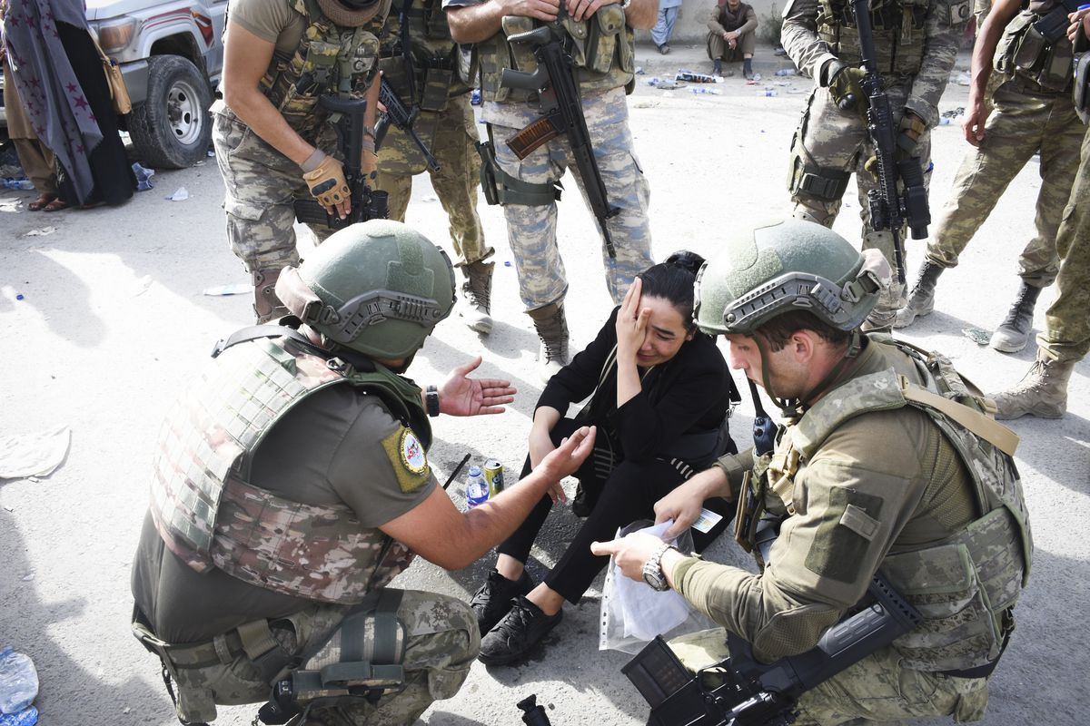 Soldiers surround a weeping woman sitting on the ground.