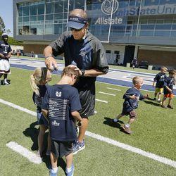 Utah State University football coach Matt Wells sprays sunscreen on his son Wyatt during a kids football camp in Logan Friday, June 12, 2015.