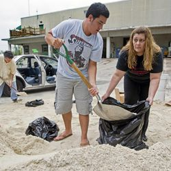 Connie Rivero and her son Anthony Amador fill plastic bags with sand at the Hollywood Public Works Department as they prepare for possible floods from Tropical Storm Isaac on Saturday, Aug. 25, 2012, in Hollywood, Fla. Isaac was expected to pass over the Florida Keys as a hurricane late Sunday or early Monday. (AP Photo/The Miami Herald, Al Diaz)