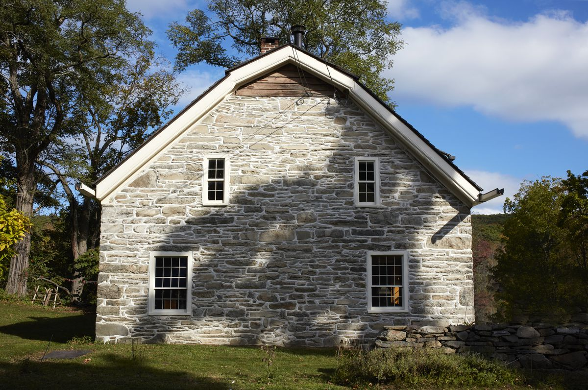 A photograph shows the stone exterior and a gambrel roof.