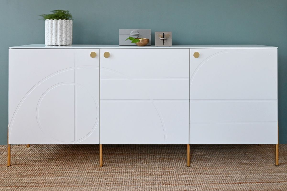 A white Ikea storage cabinet has a swooping geometric front and gold legs.