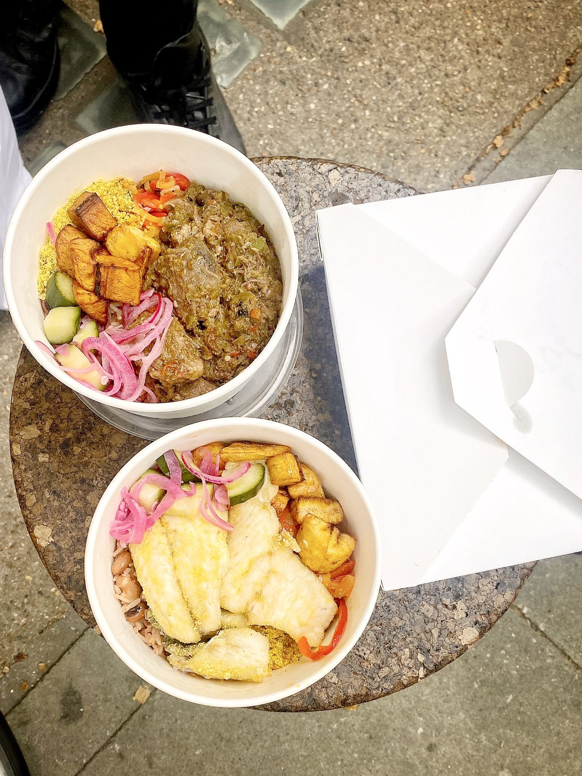 Goat amayase (top) and seabass (bottom) with pickled onions, over atassi and fufu, in white tubs on a stool, seen outside on a London pavement