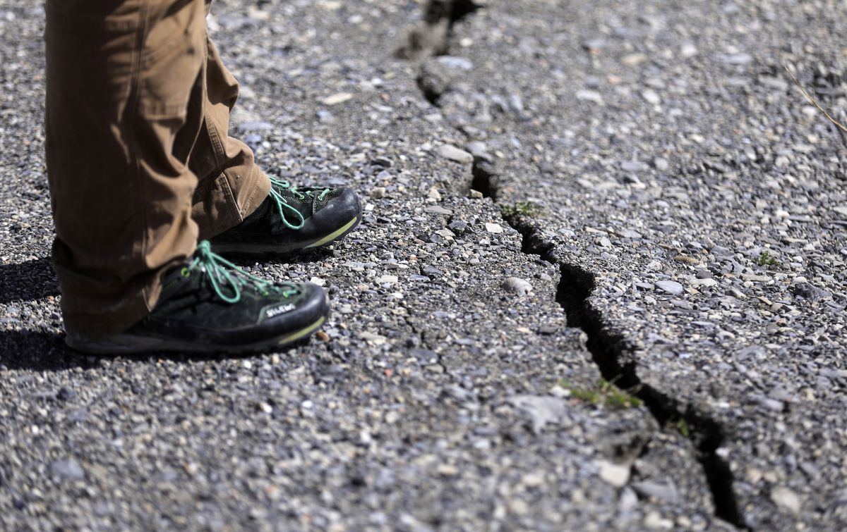 Utah Geological Survey hazards geologist Adam Hiscock looks at a crack in the road to the Great Salt Lake Marina that was likely caused by Wednesday's 5.7 magnitude earthquake with its epicenter near Magna on Thursday, March 19, 2020.