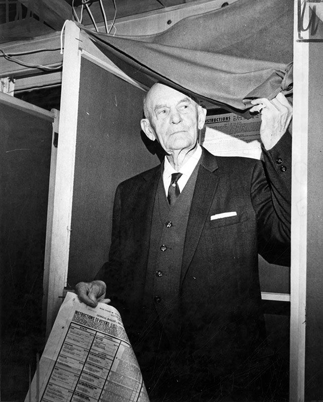 """Photograph caption dated November 6, 1962 reads: """"George Wampler, 93, was the first person to vote in his precinct, No. 2690, in North Hollywood today, and he didn't mind telling people he's been voting since 1892, when he cast his ballot for Grover Cleveland. Wampler is one of more than two million Los Angeles County voters expected to go to the polls today."""""""