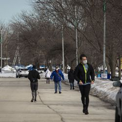 People walk and park on a portion West Montrose Avenue east of Lake Shore Drive that had been closed since March amid fears of the coronavirus pandemic, Tuesday, Feb. 23, 2021. The Chicago Park District announced plans Tuesday to gradually reopen the city's lakefront, playgrounds and indoor swimming pools in response to sustained declines in COVID-19 positivity rates and cases.