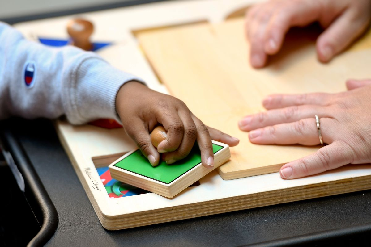 The hand of a young boy works on a small puzzle exercise with assistance from his teacher, whose hands steadies the puzzle.