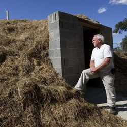 In this April 23, 2012, photo Freddie Wooten stands in front of the storm shelter he built at his own expense in Henager, Ala., following the 2011 tornado. When deadly twisters chewed through the Midwest and South in 2011, thousands of people in the killers' paths had nowhere to hide. Now many of those families are taking an unusual extra step to be ready next time: adding tornado shelters to their homes.