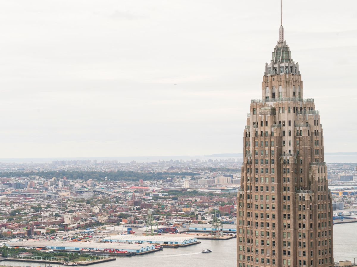 A landscape photo of the top spire of a building against the backdrop of New York City