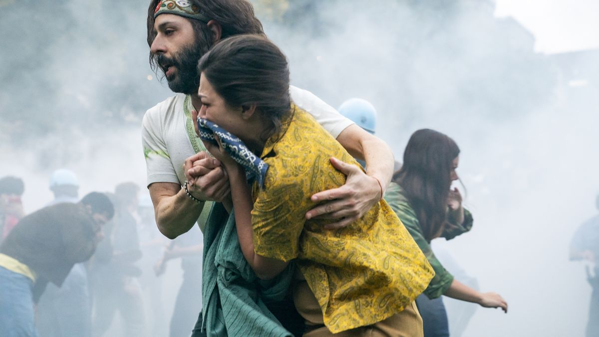 a man and woman try to get through tear gas