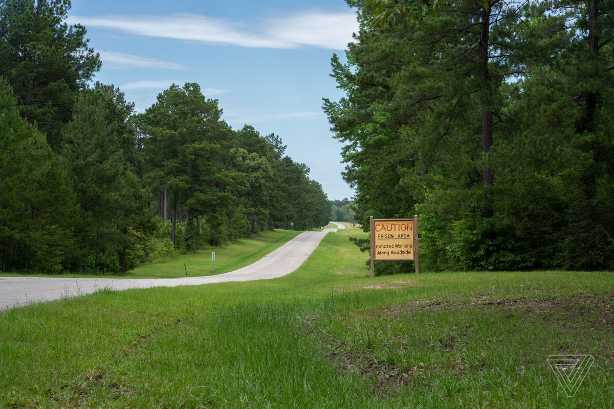 """A small sign on a rural road reads """"Caution prison area. Inmates working along roadside."""""""
