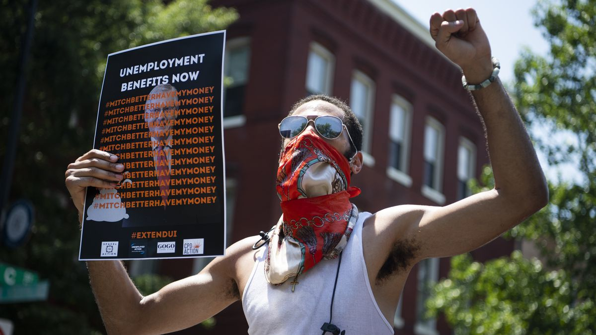"""A worker holding up a photo of Mitch McConnell at a protest. Over the photo of McConnell are the words, """"Unemployment benefits now. Mitch better have my money."""""""
