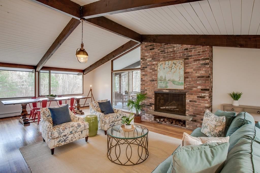 An open living room with a peaked ceiling and a large brick fireplace.