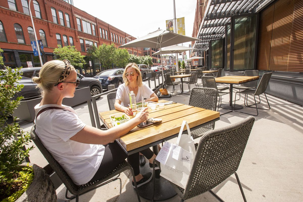 Two people sitting at patio table.