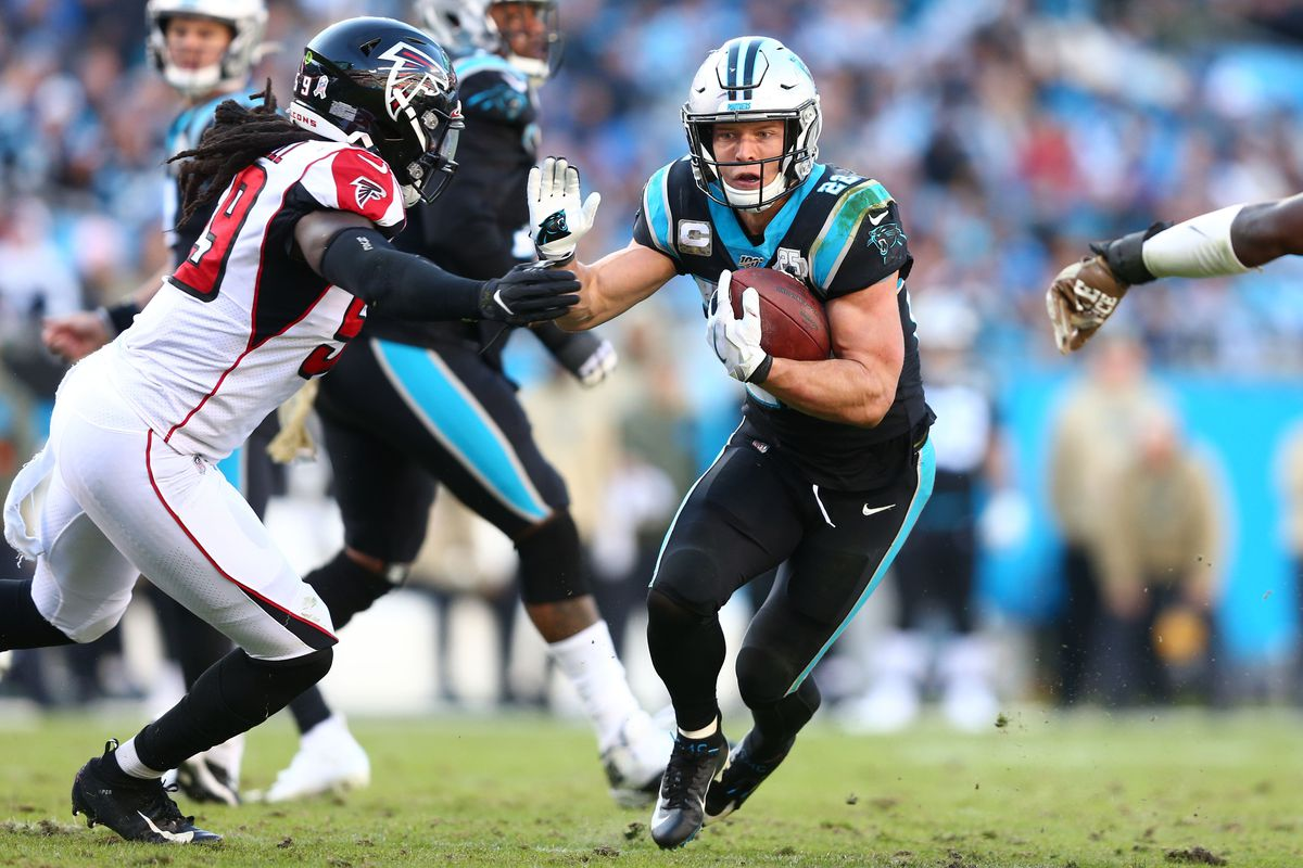 Carolina Panthers running back Christian McCaffrey carries the ball as Atlanta Falcons outside linebacker De'Vondre Campbell defends during the third quarter at Bank of America Stadium.
