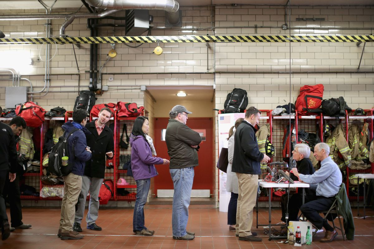 Voters wait in line at a fire station. They are not six feet apart in line, as the CDC currently recommends.