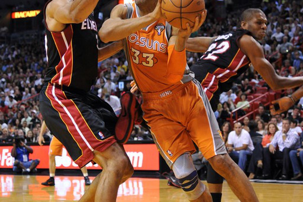 March 20, 2012; Miami, FL, USA; Phoenix Suns small forward Grant Hill (33) looks to pass around Miami Heat small forward Shane Battier (31) during the first half at American Airlines Arena. Mandatory Credit: Steve Mitchell-US PRESSWIRE