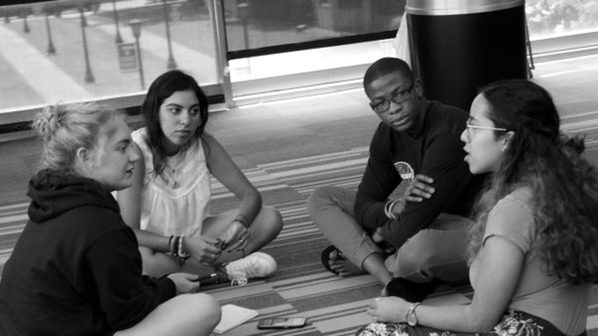 Four students sit on a classroom floor. One student is speaking and the other three are listening. They are participating in a Narrative 4 Story Exchange.
