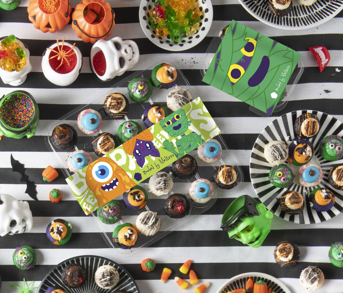 Several colorful Halloween colored cupcakes placed on a table