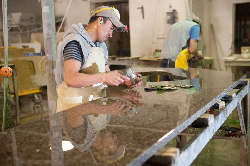 A worker sands granite after it's been cut