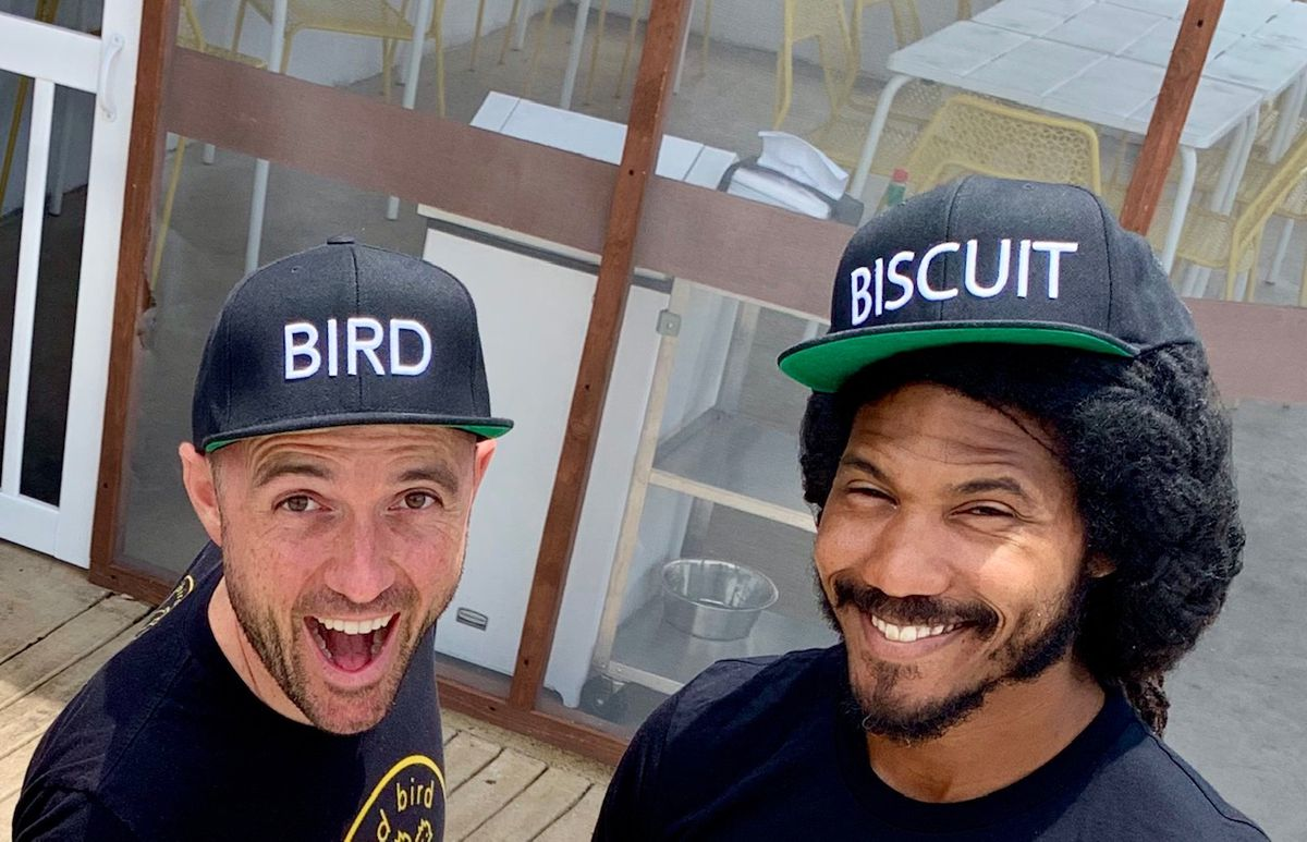 """A white man wearing a black shirt and a black baseball hat that reads """"BIRD"""" in white text standing next to a Black man in a black shirt and a black baseball hat that reads """"BISCUIT"""" in white text."""