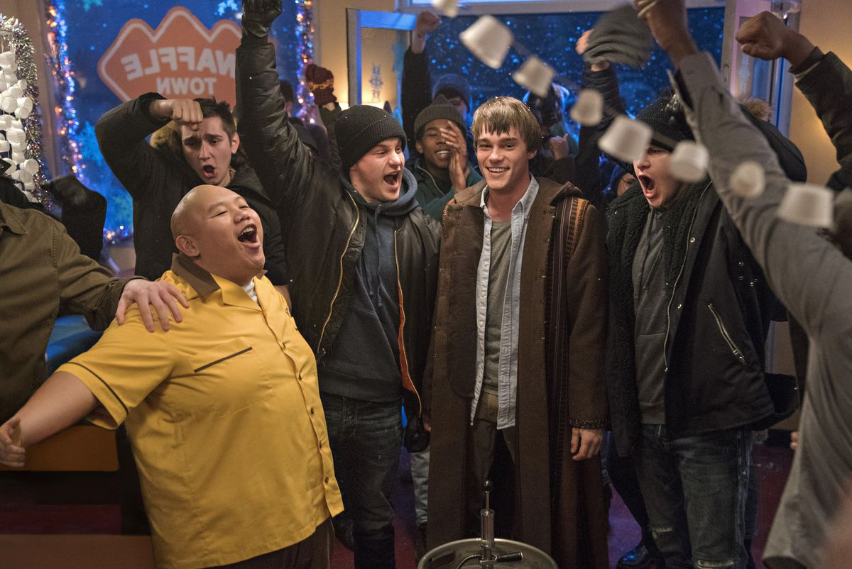 A bunch of teenagers cheer around Tobin (Mitchell Hope).