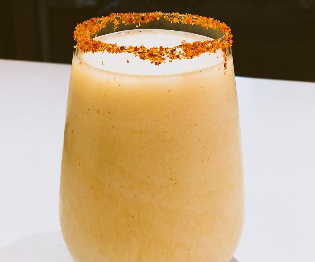 A pale orange frozen drink sits in a stemless glass with a red salt on the rim