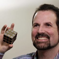 Jeweler Fred Cuellar holds a gold and gemstone version of the Rubik's Cube at Liberty Science Center, Wednesday, April 25, 2012, in Jersey City, N.J. The center will have an exhibit on the toys and will include the diamond version, which is worth 2.5 million dollars.
