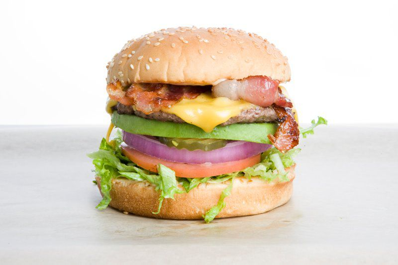 A cheeseburger at Rain City with lettuce, tomato, and onions.