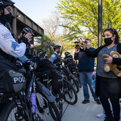 Garciela Garcia offers a Chicago police officer a stuffed animal as a peace offering outside the Chicago Police Training Academy, Friday, April 30, 2021.
