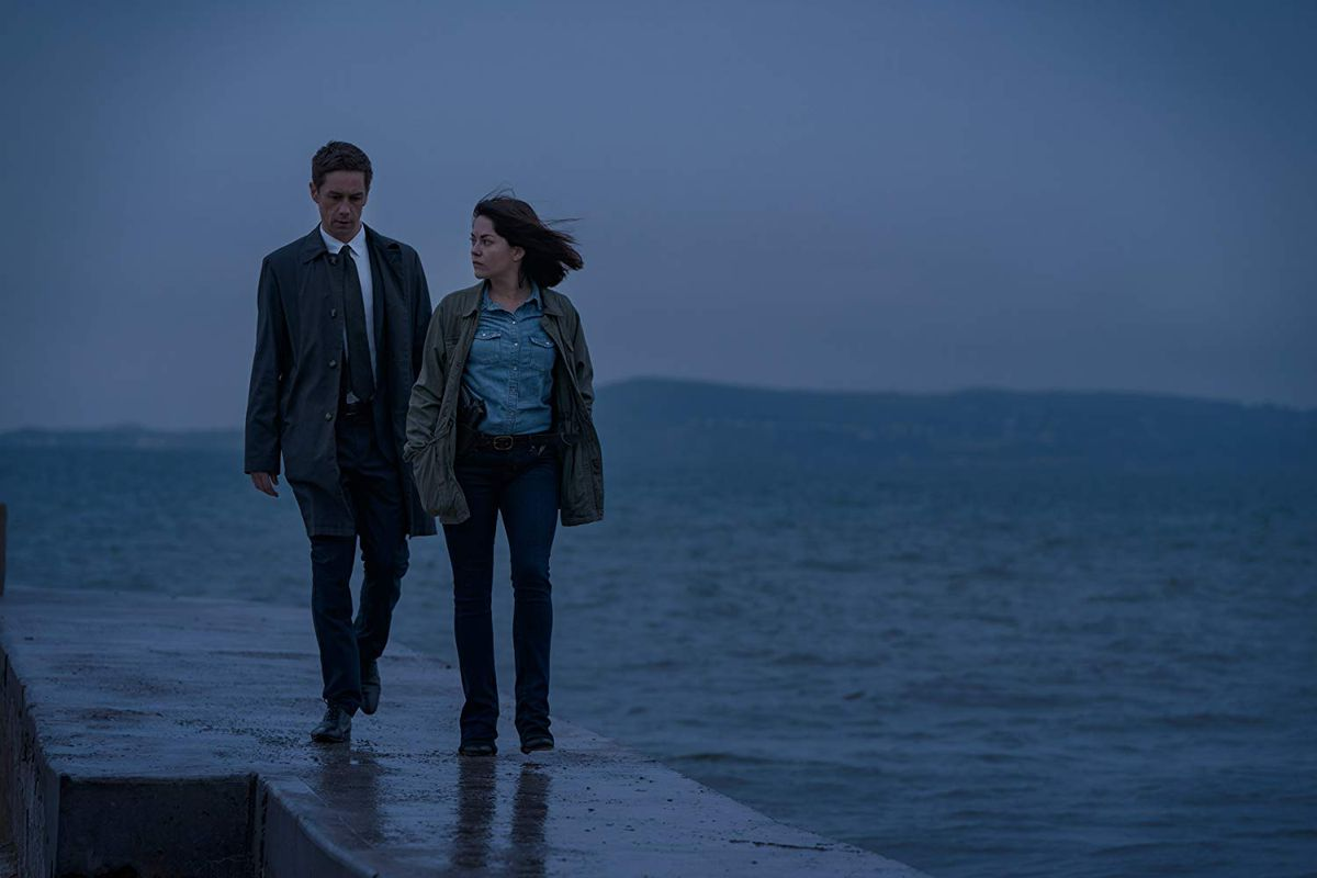 A man and a woman walk next to the sea at twilight