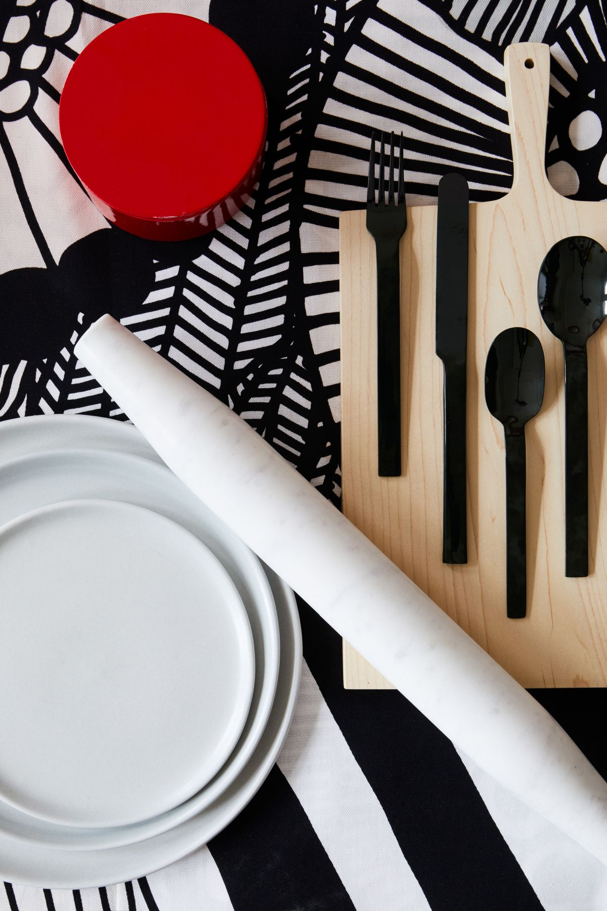 A rolling pin and other assorted tableware on a table with an abstract black and white patterned surface.